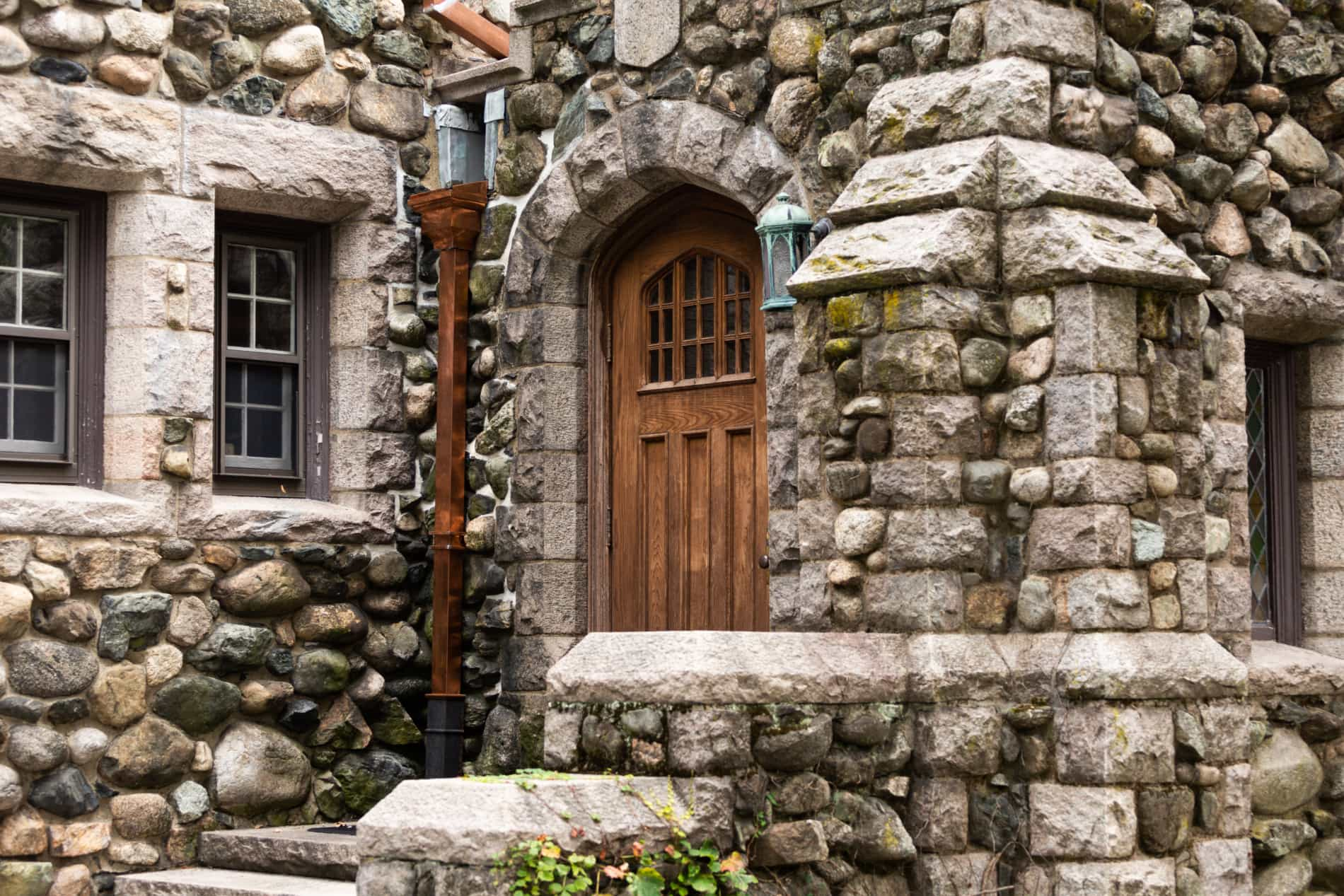A stone church with a wooden door and a copper lantern