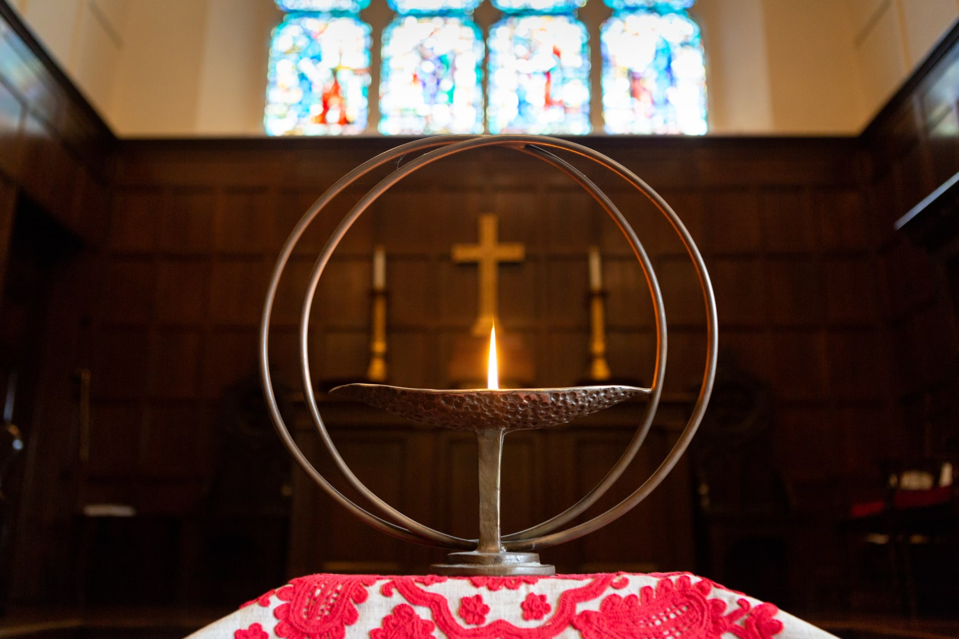 The Unitarian flaming chalice with a cross in the background